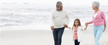 Una pareja de adultos mayores sonriendo, caminando por la playa cogidos de la mano de una niña pequeña.