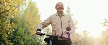 Adulto mayor en un parque sosteniendo el manubrio de su bicicleta.